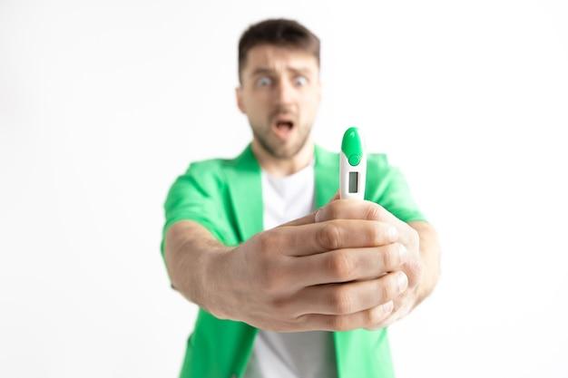 妊娠検査で見ている動揺した男。人間の感情の概念