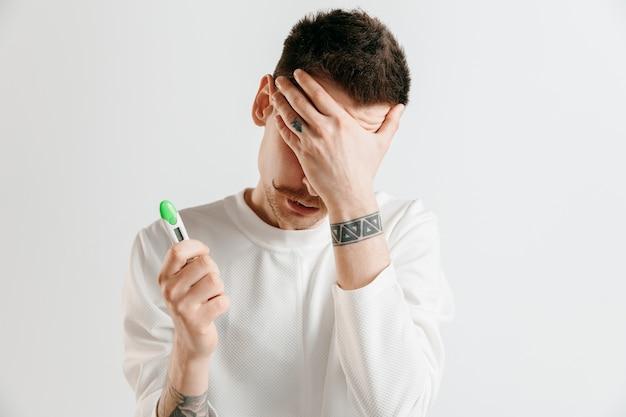 妊娠検査で見ている動揺した男。