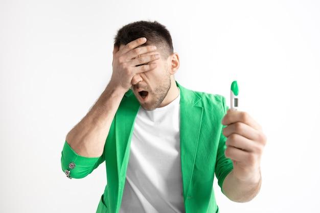 Uomo turbato che osserva nel test di gravidanza. concetto di emozioni umane