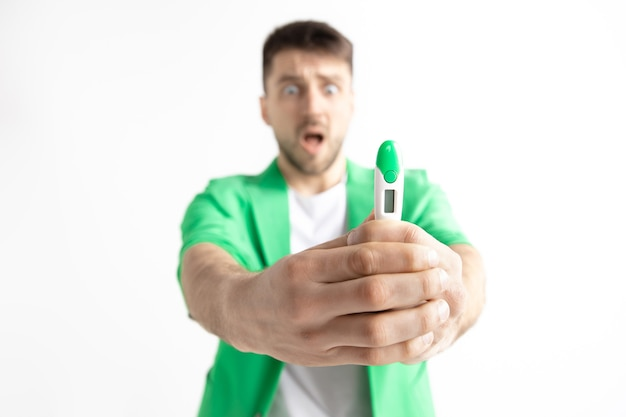 Upset man looking in pregnancy test. human emotions concept