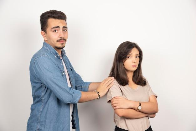 Uomo turbato e donna risentita su bianco.