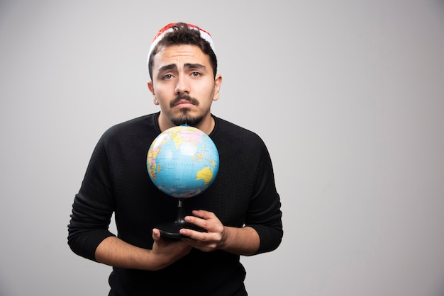 Upset man in santa's hat posing with a globe.