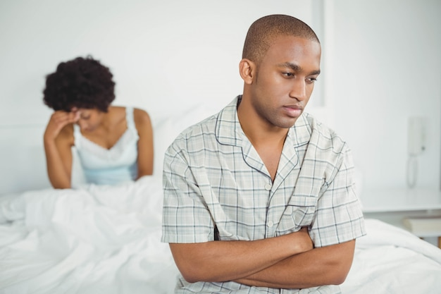 Upset man sitting on bed after arguing with his girlfriend