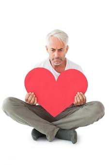 Upset man sitting holding heart shape
