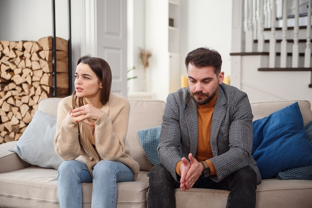 Upset man at table and woman with shopping bags in room. money problems in relationship