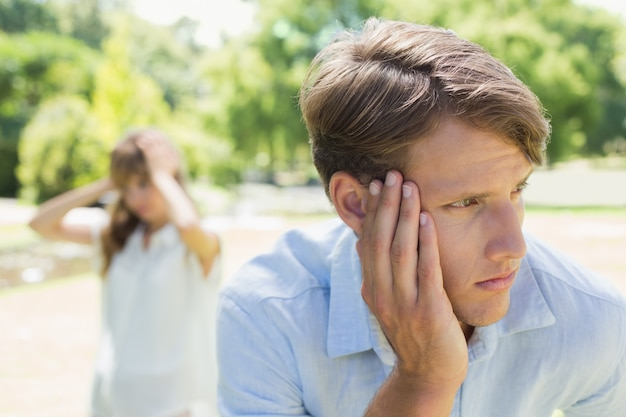 Upset man thinking after a fight with his girlfriend in the park