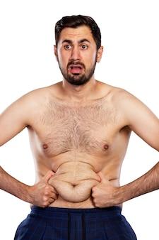 おなかの脂肪で動揺した男。スポーツマンらしくない姿。白い背景で隔離。垂直。