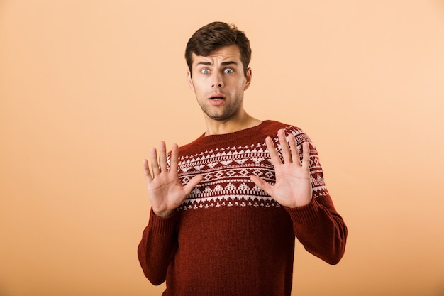 Upset man with stubble wearing knitted sweater doing stop gesture with hands, isolated over beige wall