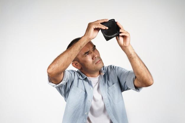 화가 난 성숙한 남자는 흰색 배경에 있는 빈 지갑을 들고 안을 들여다보고 있습니다. 금융 위기, 파산, 돈 없음, 나쁜 경제 개념.