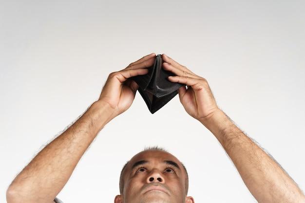 화난 성숙한 남자는 거꾸로 들고 흰색 배경에 있는 빈 지갑 안을 들여다보고 있습니다. 금융 위기, 파산, 돈 없음, 나쁜 경제 개념.