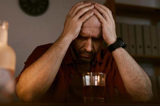テーブルに座って、手で頭を抱えている動揺した成熟した男性は、アルコールに問題があります
