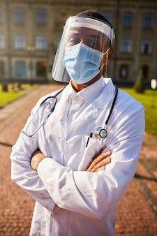 병원 앞에 서있는 동안 카메라를 들여다 보는 화가 의사