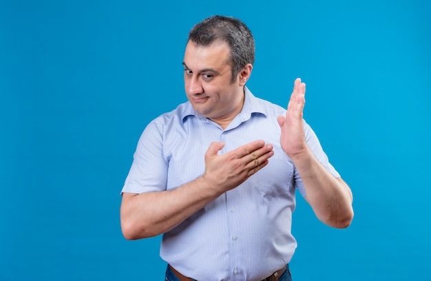 Upset middle-aged man in blue striped shirt showing with index finger to the center of palm on a blue background