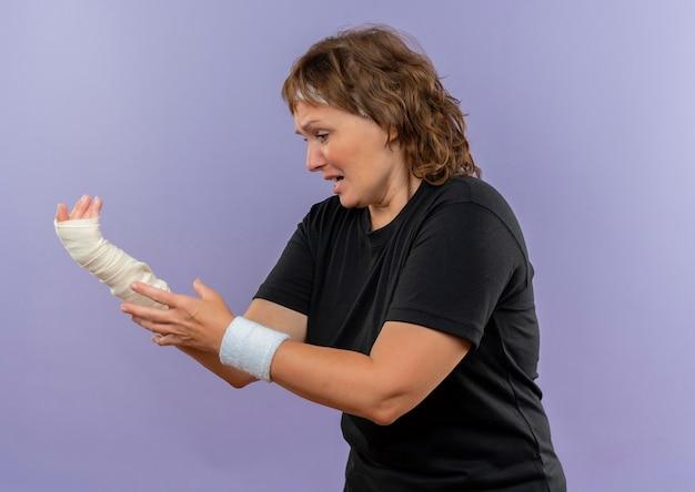 Donna sportiva invecchiata centrale sconvolta in maglietta nera con la fascia che tiene il suo polso fasciato che ha dolore che sta sopra la parete blu