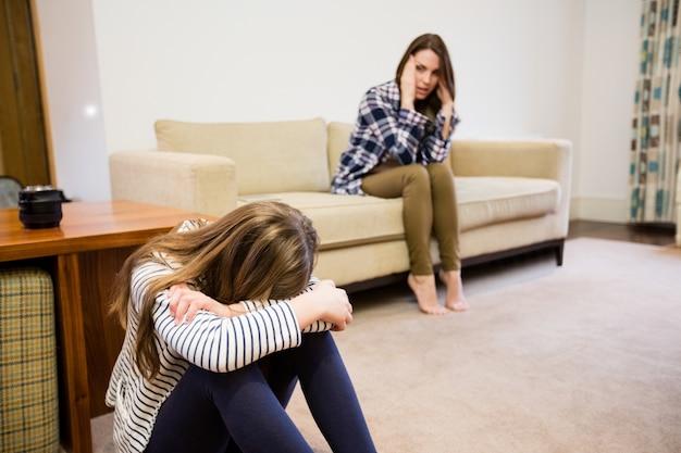 Расстроенная мать и дочь, сидя в гостиной