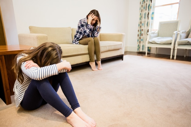 Upset mother and daughter sitting in living room