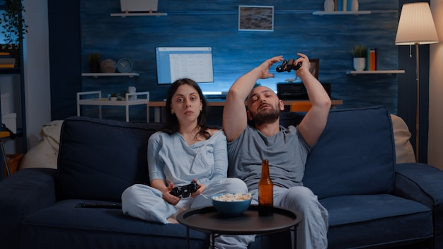 조이스틱을 사용하여 온라인 비디오 게임 경쟁에서 지는 신경질적인 커플