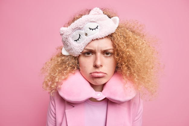 Upset offended beautiful woman with curly hair looks sadly hates early awakening wears sleepmask travel pillow around neck has miserable face expression isolated over pink wall