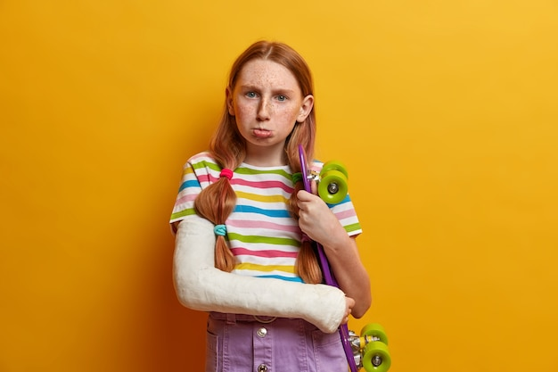 Upset offended girl going to cry, poses with skateboard, wants to have active summer holidays, has broken arm in bandaged cast, leads sporty lifestyle, has broken arm after doing dangerous trick