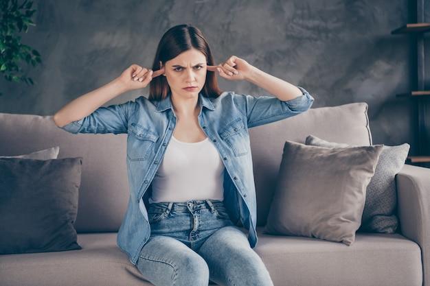 Расстроенная обиженная дама прикрывает уши пальцами, хмурясь