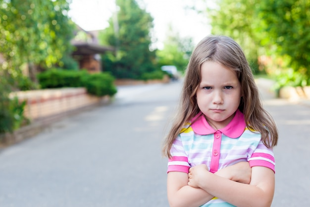 Upset or offended little girl 5 years standing on street near home. escape from the house. relation problems concept.