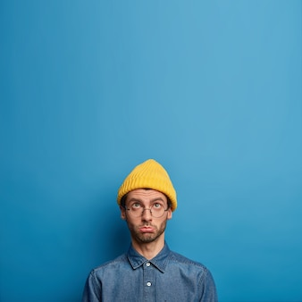 Upset offended man focused above, complains of hard life, wears yellow hat and denim shirt, looks up with sad face