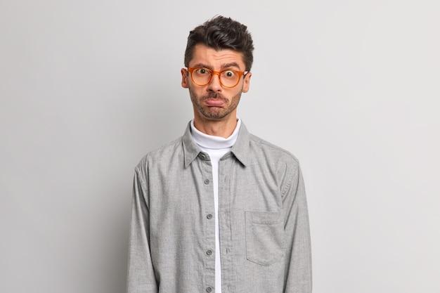 화가 난 남자 지갑 입술은 카메라에 실망 해 보이는 부정적인 감정을 표현하며 회색 배경에 불만을 나타냅니다.