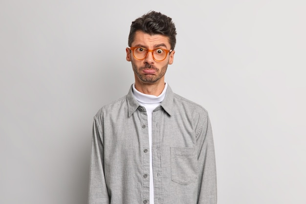 L'uomo offeso sconvolto porta le labbra sembra deluso alla telecamera esprime emozioni negative sta scontento su sfondo grigio