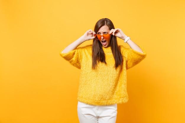 毛皮のセーター、明るい黄色の背景で隔離された脇を見てハートオレンジ色のメガネを保持している白いズボンで気分を害した若い女性を動揺させます。人々の誠実な感情、ライフスタイルのコンセプト。広告エリア。