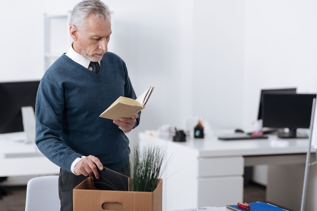 黒いノートを箱に入れて職場の近くの半位置に立っている動揺したサラリーマン