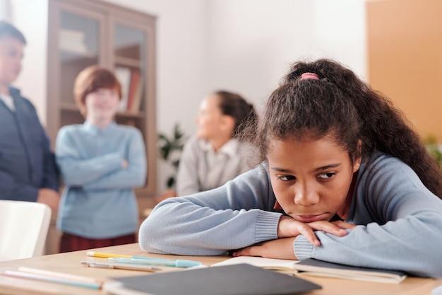 Расстроенная или обиженная школьница сидит за партой и держит за тетрадку подбородок и руки