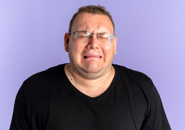 Upset overweight man in glasses wearing black t-shirt with unhappy face going to cry standing over blue wall