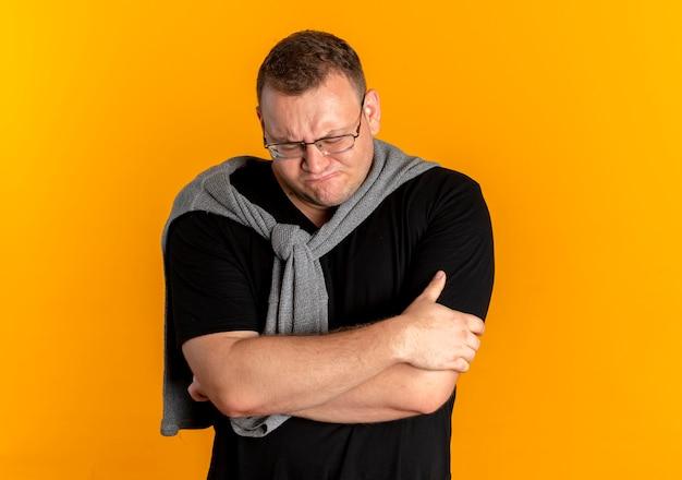 オレンジ色の壁の上に立って腕を組んで黒いtシャツを着た眼鏡で動揺した太りすぎの男