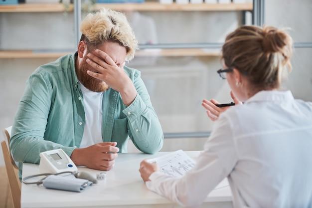 Расстроенный толстый мужчина сидит за столом и, закрывая лицо рукой, слушает диагноз ...