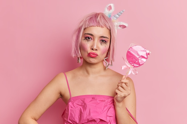 Upset pink haired young asian woman pouts lips has leaked makeup looks sadly at camera being offended by someone holds wrapped sweet candy dressed in stylish dress