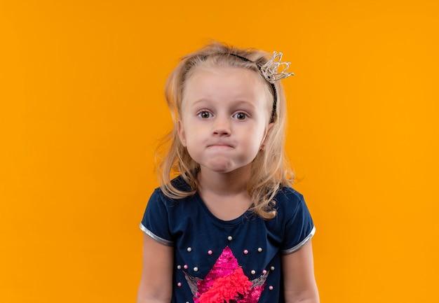 Una bambina graziosa sconvolta che indossa la camicia blu navy nella fascia della corona che osserva su una parete arancione