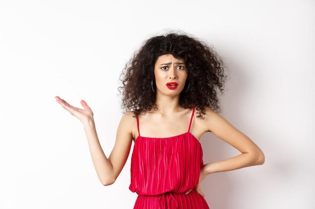 곱슬 머리와 빨간 드레스로 예쁜 여자를 화나게하고 손을 들고 혼란스러워 보이며 실망스럽고 불공평 한 일에 대해 이야기하고 흰색 배경에 서 있습니다.