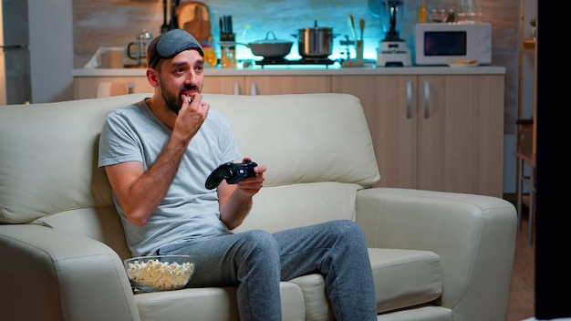 Upset pro gamer sitting on couch and playing soccer videogames