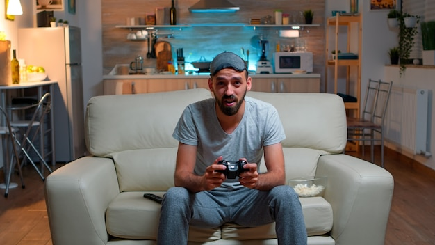 Upset pro gamer sitting in front of television losing soccer video games