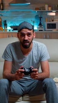 サッカーのビデオゲームを失うテレビの前に座っている動揺したプロゲーマー