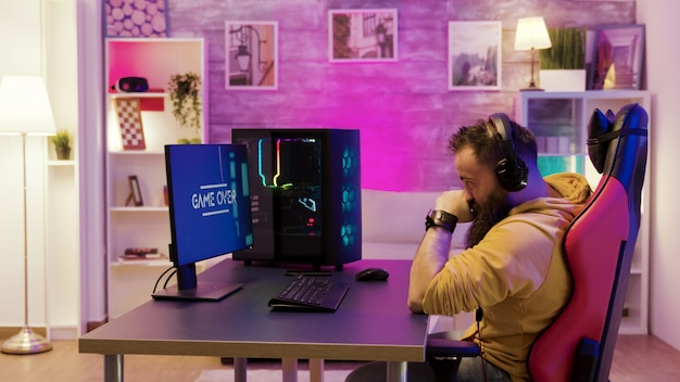重要なオンラインゲームを失った後、プロのゲームプレーヤーを動揺させます。カラフルなネオンライトのある部屋で遊ぶゲーマー。