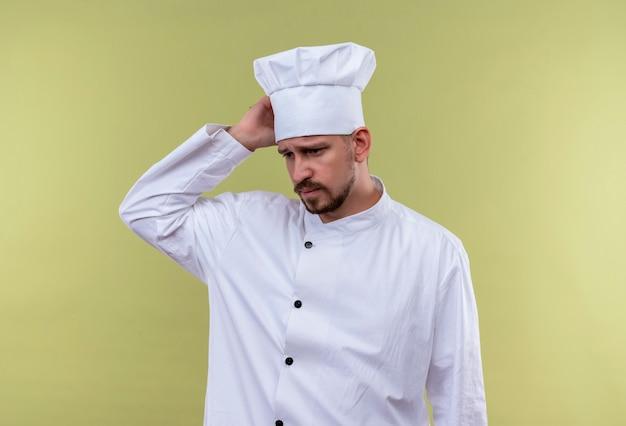 Расстроенный профессиональный шеф-повар-мужчина в белой униформе и поварской шляпе выглядит усталым и переутомленным, касаясь его головы, стоящей на зеленом фоне