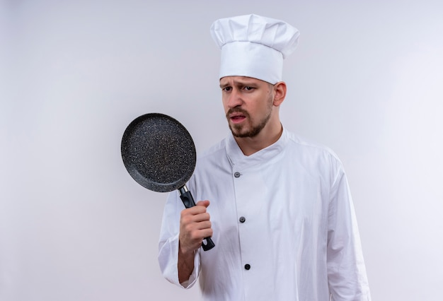 Upset professional male chef cook in white uniform and cook hat holding a pan with sad expression on face standing over white background
