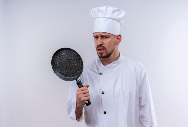 Cuoco maschio professionista sconvolto cuoco in uniforme bianca e cappello da cuoco che tiene una padella con l'espressione triste sul viso in piedi su sfondo bianco