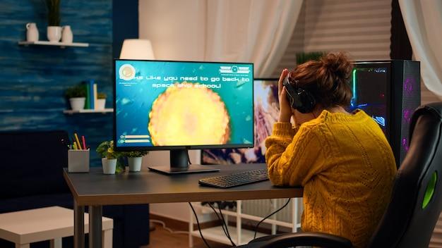 ヘッドセットを身に着けているプロの女性ゲーマーがサイバースポーツの競争でシューティングゲームのラウンドを失った動揺。疲れたプレーヤーは、最新技術のネットワークワイヤレスを備えたパーソナルコンピュータでオンラインビデオゲームをゲームします