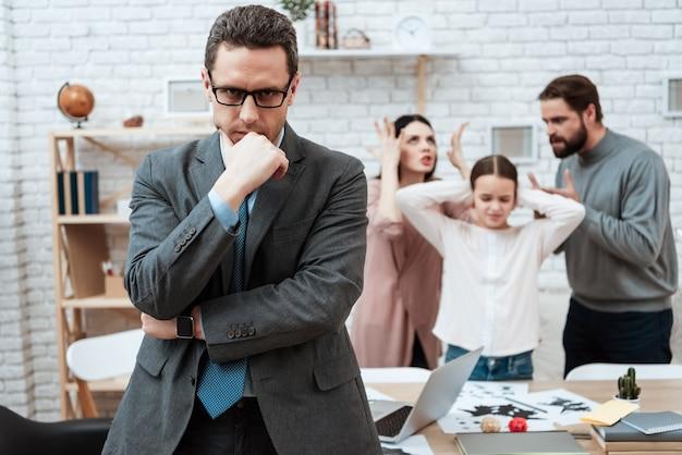 Upset psychologist thinking while family fighting