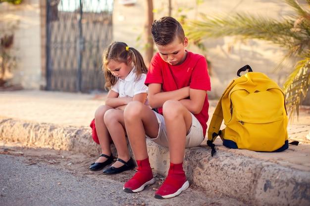 屋外で互いに腹を立てて動揺している生徒。子供との関係の概念