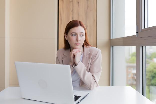 オフィスに座っているコンピューターで働く動揺した赤毛のビジネス女性