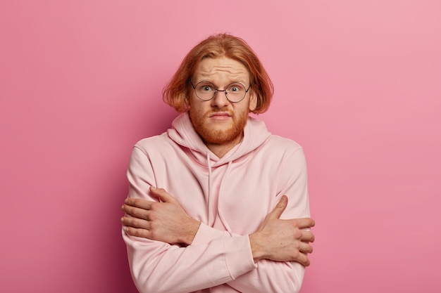 Upset redhead man crosses arms over body, tries to warm himself