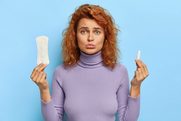 Upset redhead woman holds hygienic sanitary pad and tampon, chooses good protection during red days, has gloomy face expression, wears casual jumper, isolated on blue wall. feminity concept